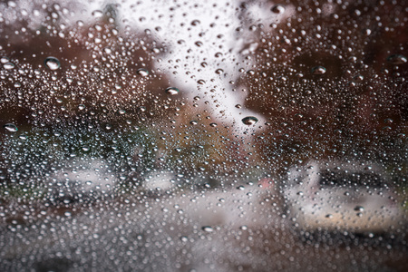 Raindrops on the windshield on a rainy day; street lined up with autumn colored trees in the background; California