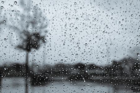 Dark and rainy day; raindrops on the windshield; tree shapes visible in the background; black and white Stok Fotoğraf