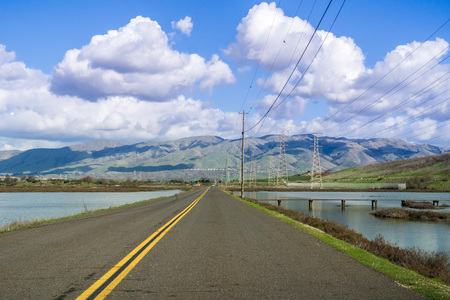 Driving through Alviso marsh towards Don Edwards National Wildlife Refuge Visitor Center located in south San Francisco bay; part of the Diablo mountain range in the background; San Jose, California