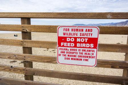 Do not feed birds sign posted on the Pacific Ocean shoreline, Pismo Beach, California