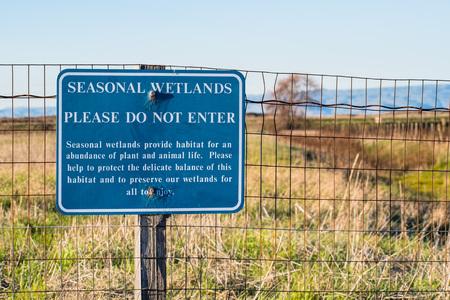 Seasonal Wetlands, please do not enter sign posted on a metal fence in Sunnyvale Baylands park, south San Francisco bay area, California Banco de Imagens