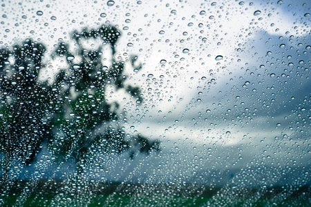 Drops of rain on the window; blurred trees and storm clouds in the background; Stok Fotoğraf