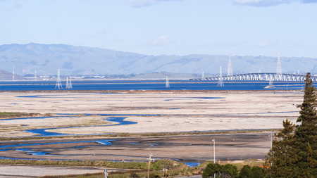 Salt accumulating on the shallow ponds of San Francisco bay at low tide, electricity towers and Dumbarton bridge in the background, California