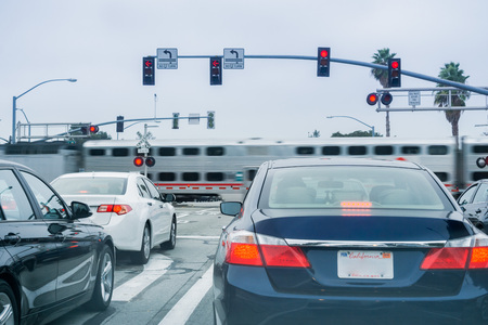 Vehicles waiting at a red traffic light; high speed train passing in the background, San Francisco bay area, California 스톡 콘텐츠