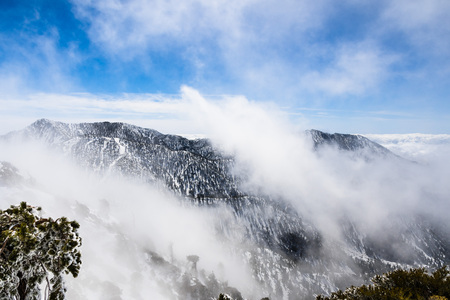 Changing weather with fog rising up from the valley, Mount San Antonio (Mt Baldy), south California Banco de Imagens