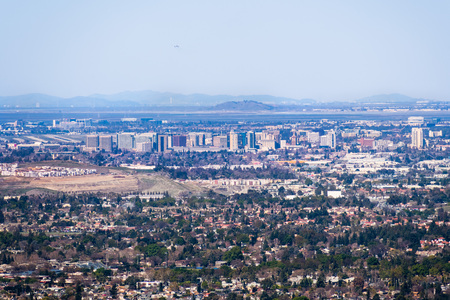 Aerial view of downtown San Jose on a clear day; residential neighborhoods in the foreground; Santa Clara and San Francisco bay in the background; Silicon Valley, California