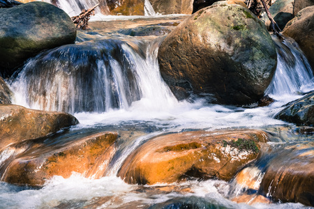 Close up of water falling through rocks on the course of a creek in Uvas Canyon County Park, Santa Clara county, California; long exposure