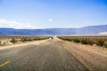 Driving through Panamint Valley; sand carried on the road by wind; Mojave Desert, California