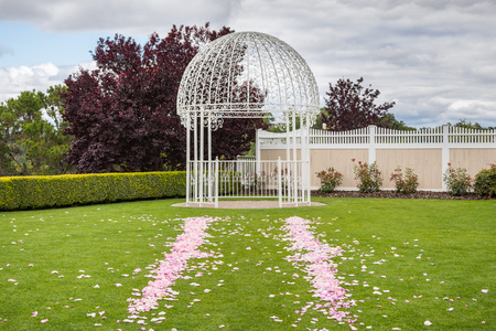 Outdoors wedding venue with forged iron wedding arch and rose petals spread on a green grass lawn; cloudy sky background