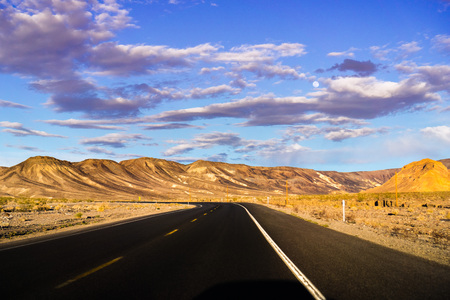 Driving through Death Valley National Park at sunset, California