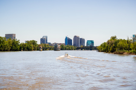 Boat cruising on the muddy looking water of Sacramento river; the City's downtown skyline in the background; California