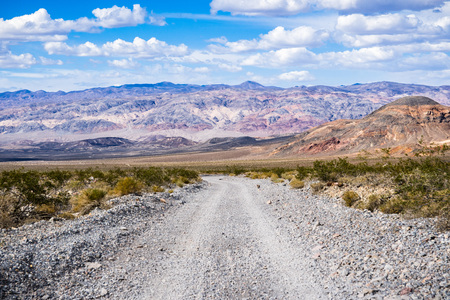 Travelling on an unpaved road through a remote area of Death Valley National Park; mountains, blue sky and white clouds in the background; California Stock Photo
