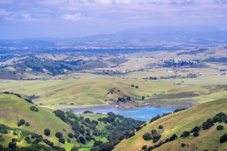 View towards San Antonio reservoir surrounded green hills; Pleasanton and Mt Diablo in the background, Alameda county, San Francisco bay area, California Banco de Imagens