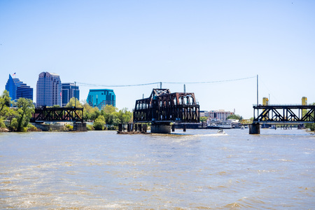 The I Street Bridge is a historic metal truss swing bridge located on I Street in Sacramento; the city's downtown skyline in the background, California