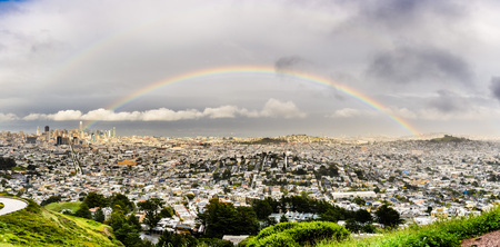 Panoramic view of San Francisco on a rainy day, rainbow stretching above the city; residential area in the foreground; the financial district and the SF bay shoreline in the background; April 2018