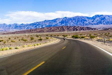 Driving through Death Valley National Park on clear morning, California
