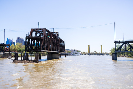 The I Street Bridge is a historic metal truss swing bridge located on I Street in Sacramento; the Tower Bridge and the city's skyline in the background; California
