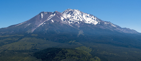 Panoramic view of the snow covered summit of Shasta mountain on a sunny summer day, California