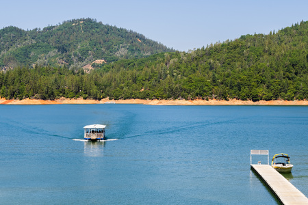Shasta Lake, McCloud River Arm landscape on a sunny summer day with ship approaching the shoreline, Northern California Stock Photo
