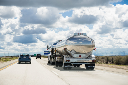 March 15 2018 Lost Hills  CA  USA - Tanker truck driving on interstate I5, the road being reflected in its shiny cistern;