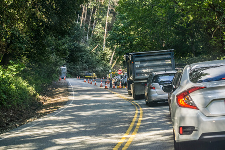 May 12, 2017 SaratogaCAUSA - Cars waiting to pass through a construction area located on a winding road in a forest, San Francisco bay area