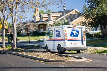 December 12, 2017 Livermore  CA  USA - USPS vehicle driving through a residential neighborhood on a sunny day