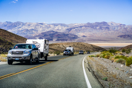 May 28, 2018 Death Valley / CA / USA - Pick up trucks with RV travel trailers driving though Death Valley National Park; Panamint Valley visible in the background
