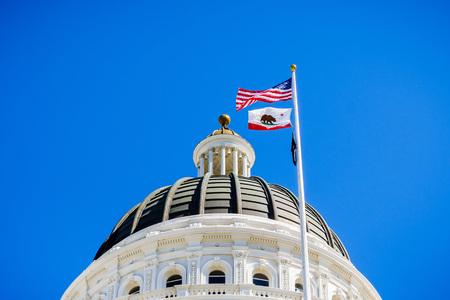 14 avril 2018 Sacramento / CA / USA - Les États-Unis et le drapeau de l'État de Californie agitant dans le vent devant le dôme du Capitole de l'État de Californie