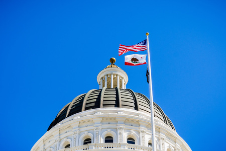 14 de abril de 2018 Sacramento / CA / EE. UU. - Los Estados Unidos y la bandera del estado de California ondeando en el viento frente a la cúpula del Capitolio del Estado de California