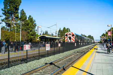 April 20, 2018 Mountain View  CA  USA - Commuters waiting on the platform to take the Caltrain towards San Francisco; Train arriving at the station
