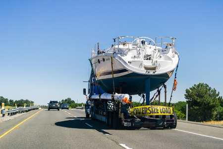 June 24, 2018 Redding / CA / USA - Truck carrying large boat on the interstate