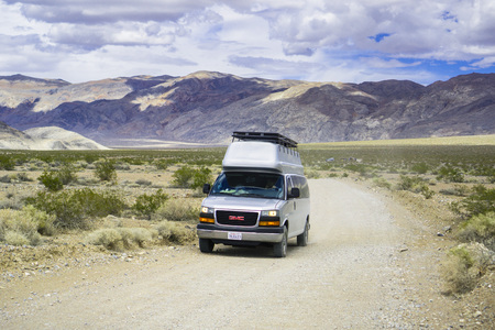 May 27, 2018 Death Valley / CA / USA - Modified GMC minivan travelling on an unpaved road through a remote area of Death Valley; converting standard vans to full-on campers is the new trend