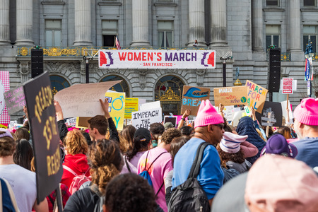 January 19, 2019 San Francisco  CA  USA - Participants to the Womens March event hold signs with various messages; the rally stage and the City Hall building visible in the background Editorial