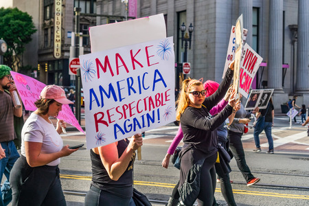 January 19, 2019 San Francisco  CA  USA - Participants to the Womens March event hold Make America Respectable Again sign while marching on Market street in downtown San Francisco