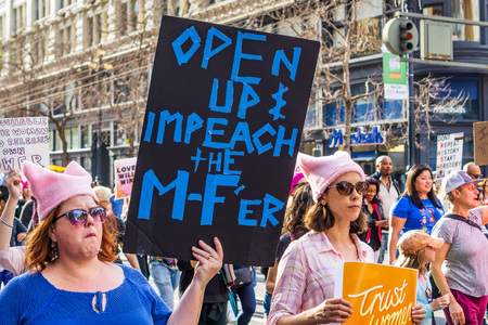 January 19, 2019 San Francisco  CA  USA - Participant to the Womens March event holds sign referencing the shutdown and impeachment while marching on Market street in downtown San Francisco Editorial