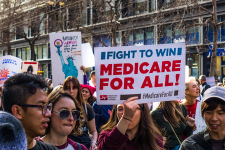 """January 19, 2019 San Francisco / CA / USA - Participant to the Women's March event holds """"Medicare for all"""" sign while marching on Market street in downtown San Francisco Sajtókép"""