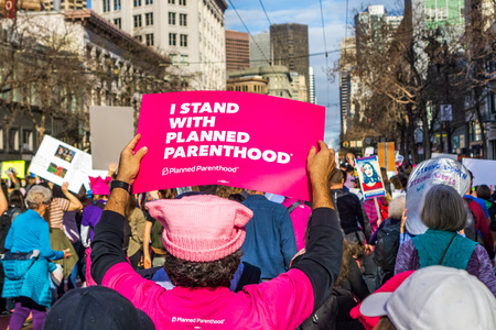 January 19, 2019 San Francisco  CA  USA - Participant to the Womens March event holds I stand with Planned Parenthood sign while marching on Market street in downtown San Francisco Redakční