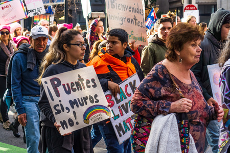 January 19, 2019 San Francisco  CA  USA - Participants to the Womens March event hold signs with various messages while marching on Market street in downtown San Francisco