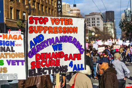 January 19, 2019 San Francisco  CA  USA - Participant to the Womens March event holds sign referencing voting suppression, gerrymandering while marching on Market street in downtown San Francisco Editorial