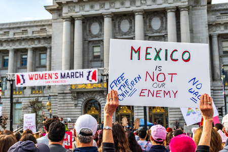January 19, 2019 San Francisco  CA  USA - Participant to the Womens March event holds Mexico is not our enemy sign; the City Hall building visible in the background
