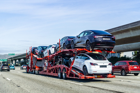 January 19, 2019 San Bruno  CA  USA - Car transporter carries Tesla Model 3 new vehicles along the highway in San Francisco bay area, back view of the trailer; Redakční