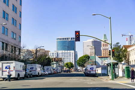January 27, 2019 Oakland  CA  USA - Landscape in downtown Oakland, east San Francisco bay area; USPS vehicles parked on both sides of the road Editorial