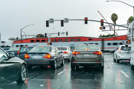 2 febbraio 2019 Sunnyvale/CA/U.S.A. - Veicoli che aspettano ad un semaforo rosso; Treno ad alta velocità che passa in background, area della baia di San Francisco, California