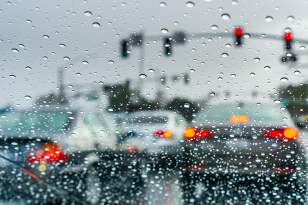 Raindrops on the windshield on a rainy day; cars stopped at a traffic light in the background; California Foto de archivo