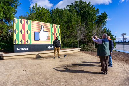 February 10, 2019 Menlo Park  CA  USA - Group of people taking photos with the Facebook logo (customized for black history month) located outside the Companys main campus in Silicon Valley;
