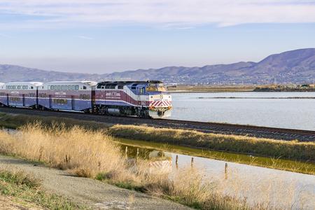 December 6, 2016, Altamont commuter express - Ace, San Jose, California, USA - Train passes through Alviso marsh on a sunny morning