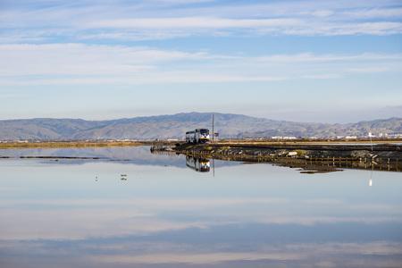 December 6, 2016, Alviso, San Jose, California, USA - Amtrak train passes through Alviso marsh on a sunny day