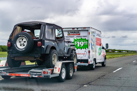 March 20, 2019 Los Angeles  CA  USA - U-Haul van travelling on the interstate, hauling a Jeep; U-Haul is an American company offering DIY moving solutions