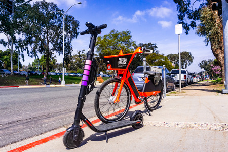 March 19, 2019 San Diego  CA  USA - Jump Electric Bike (owned by Uber) and Lyft Escooter parked side by side on the sidewalk, near parked near Balboa Park; Editorial