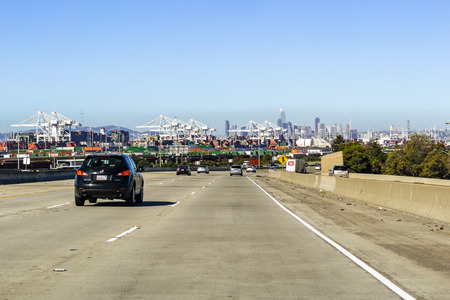March 31, 2019 Oakland / CA / USA - Travelling on the freeway in east San Francisco bay area; Port of Oakland and the San Francisco skyline visible in the background